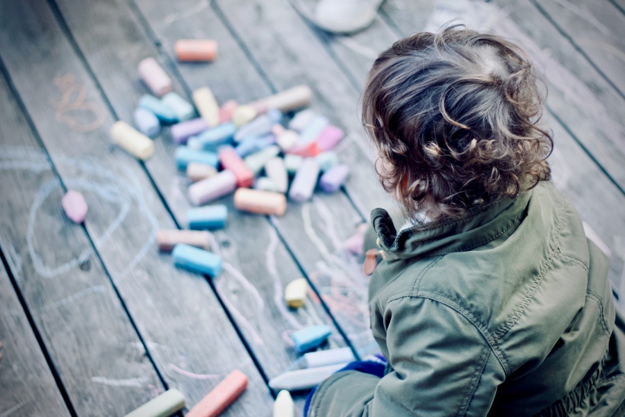 child playing with color chalk